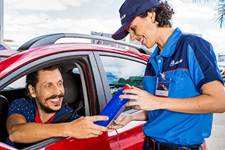Frentista do posto ALE vende lubrificante de qualidade, da marca Mobil, para homem que está sorrindo dentro de seu carro, que é vermelho