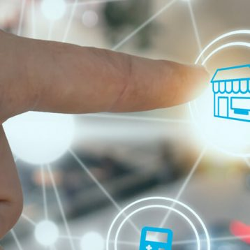 Mão humana toca em imagem holográfica que representa um comércio.
