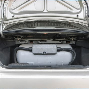 Carro sedã prata com cilindro de GNV cinza no porta malas