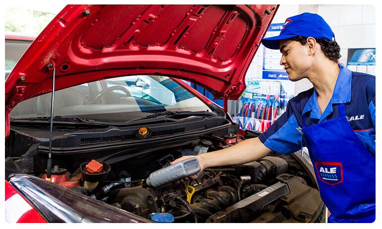 Frentista da loja de serviços automotivos ALE Express faz a troca de óleo de um carro vermelho.