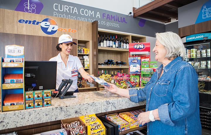 Atendente mulher da loja de conveniência Entreposto atende mulher de cabelos brancos, ambas sorrindo