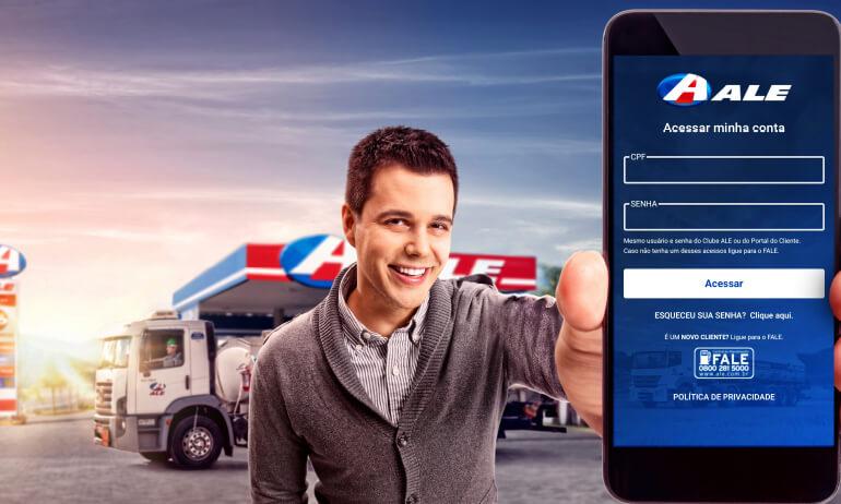 Homem caucasiano sorri enquanto mostra a tela de login do App ALE Combustíveis para a tela, ao fundo há um posto de combustível.